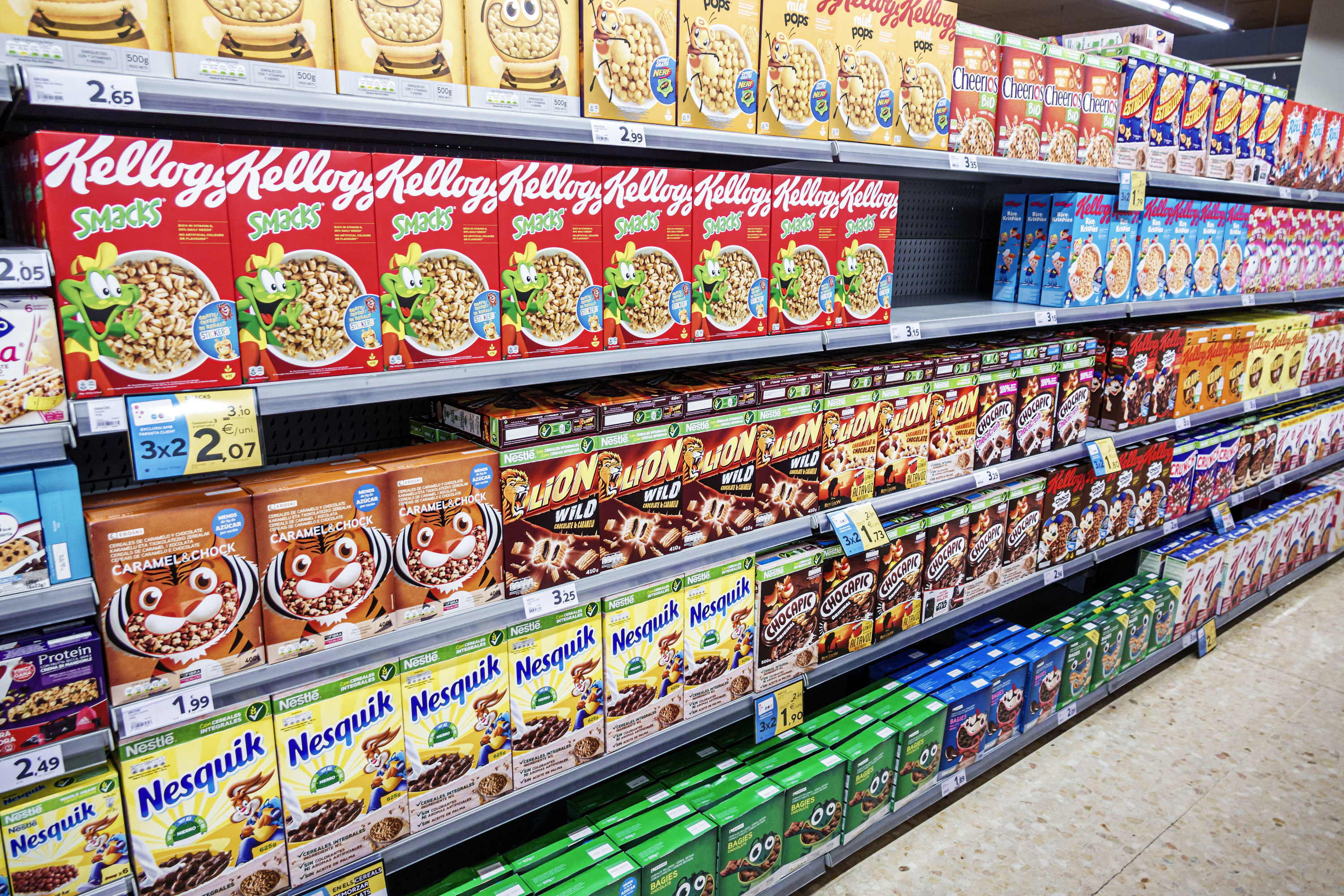 Grocery store aisle with multiple shelves stocked with different colorful cereal boxes