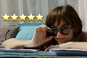 ana from 50 shades of grey relaxing at a resort by the pool with 5 stars next to her