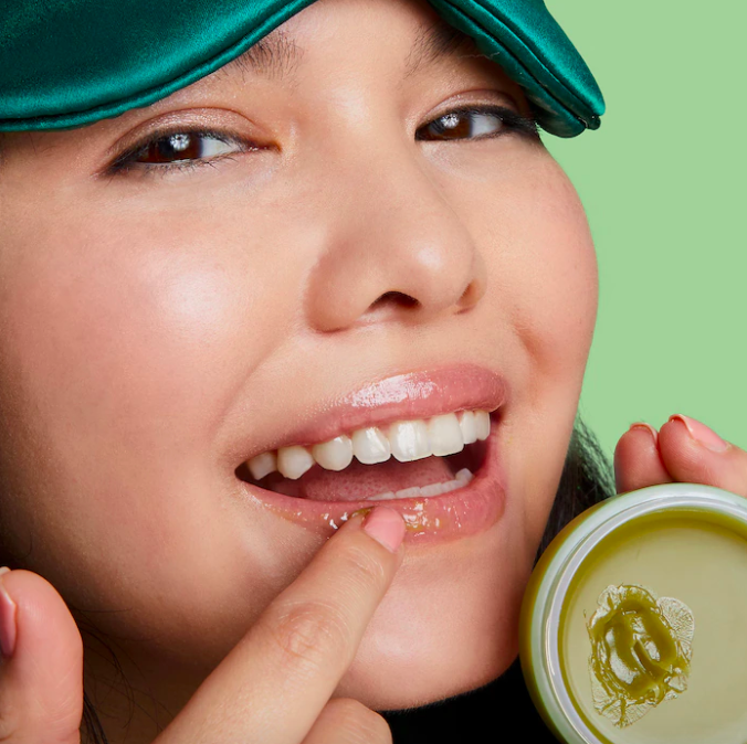 A smiling person applying the green tea mask to their lips