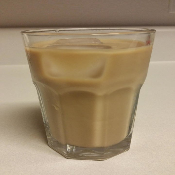 A reviewer photo of a clear glass filled with ice coffee made in the pitcher