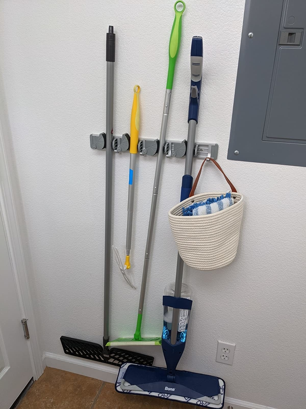 The rack, which holds mops, rooms, and even bags from a series of small, adjustable hooks