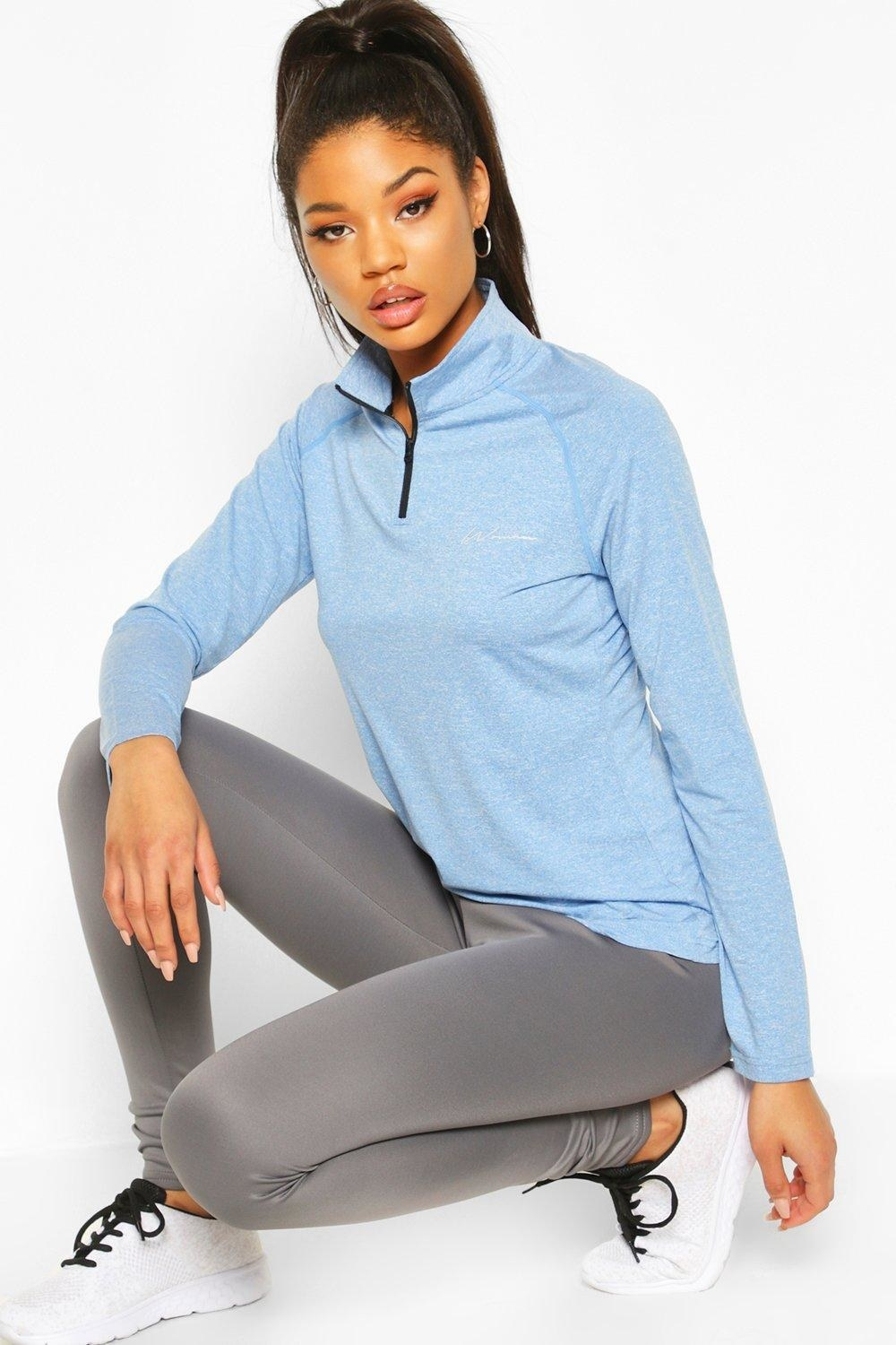 a model wearing the blue sweater with a funnel neck