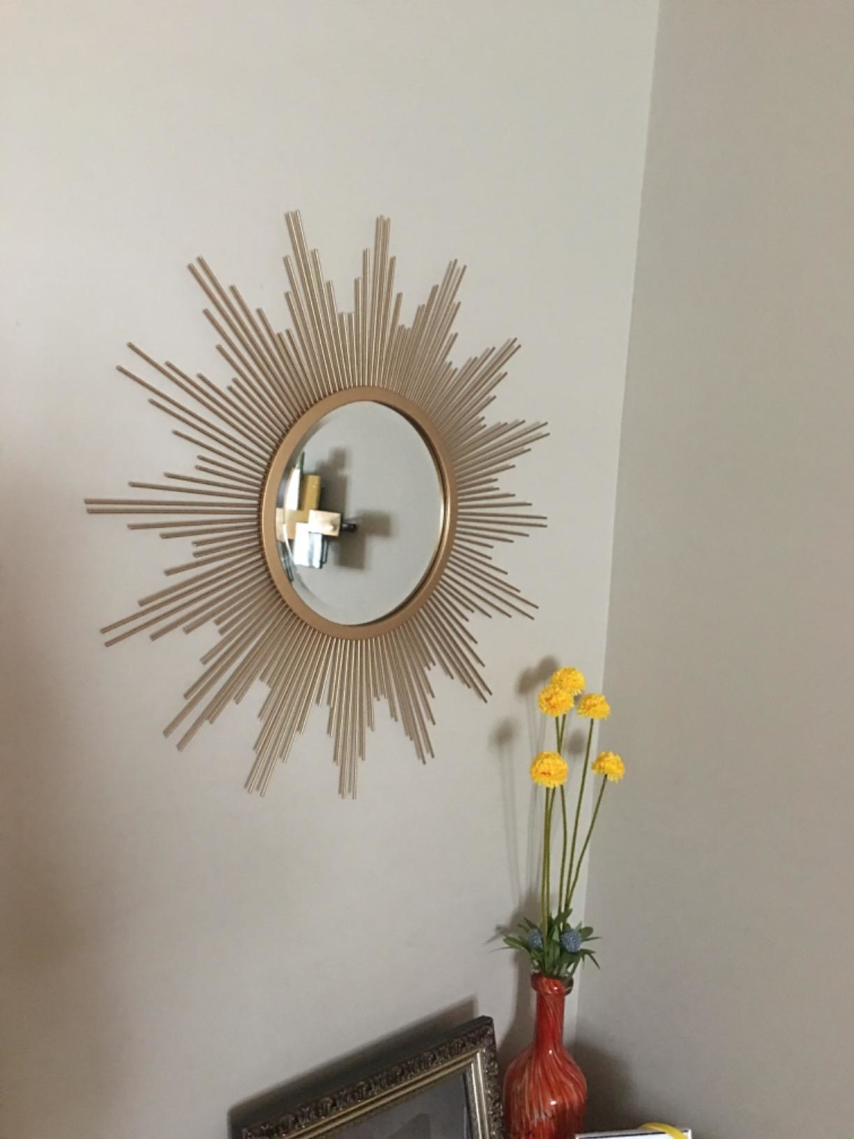 reviewer image of the stonebriar sunburst wall mirror mounted on a wall above an accent table with flowers in a vase