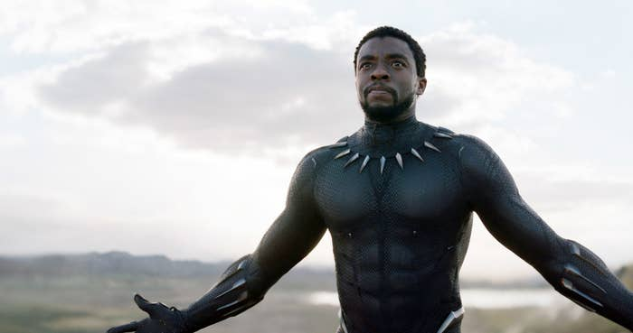 Boseman with his arms raised in Black Panther