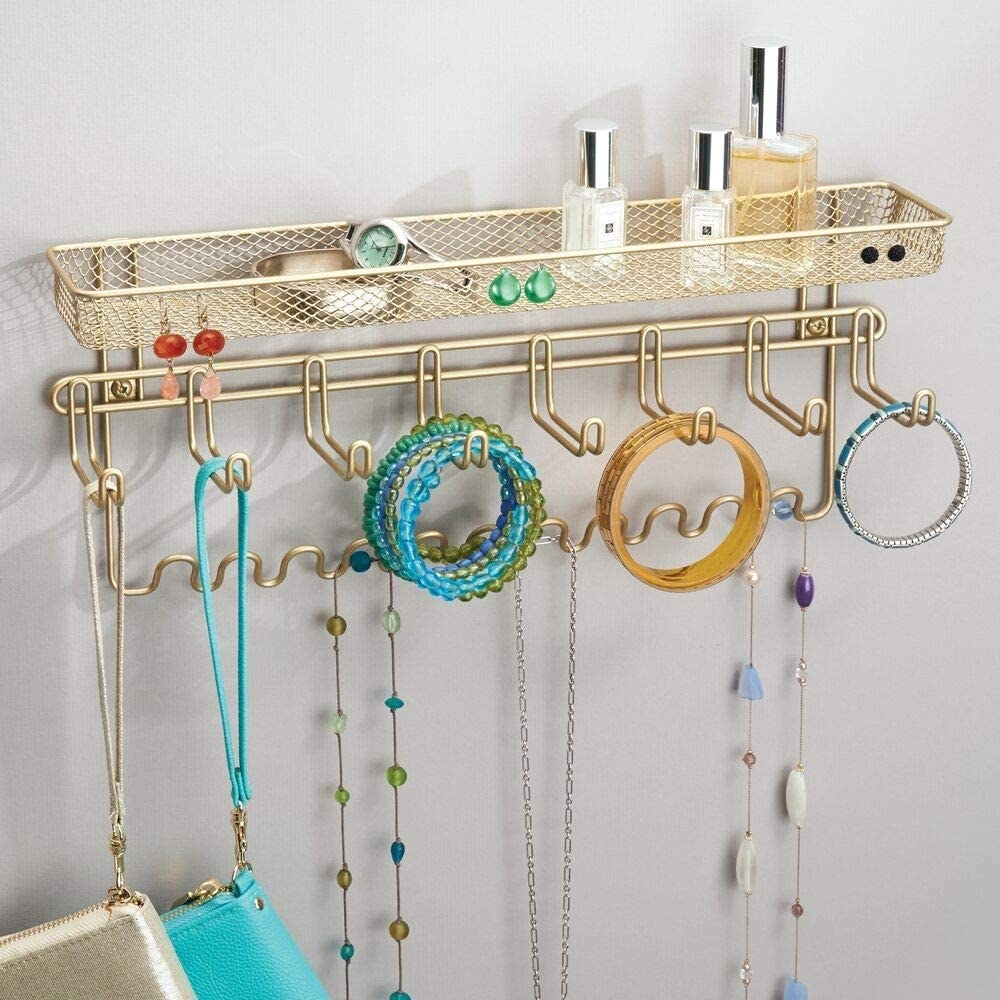 The gold mDesign Closet Wall Mount Men's Accessory Storage Organizer Rack holding jewelry and clutches