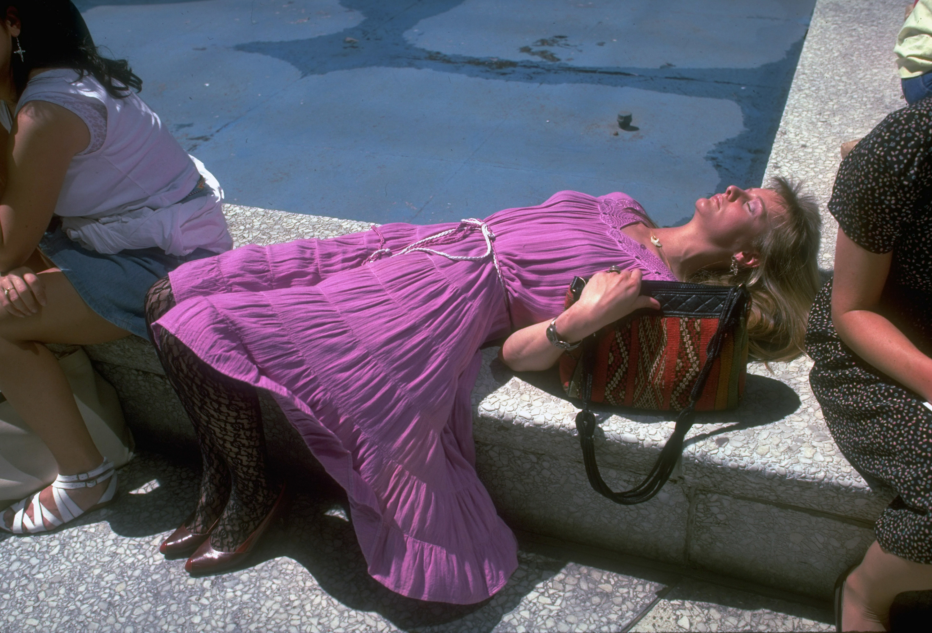 Pink dress-clad woman sunbathing with vigilant hand on her purse