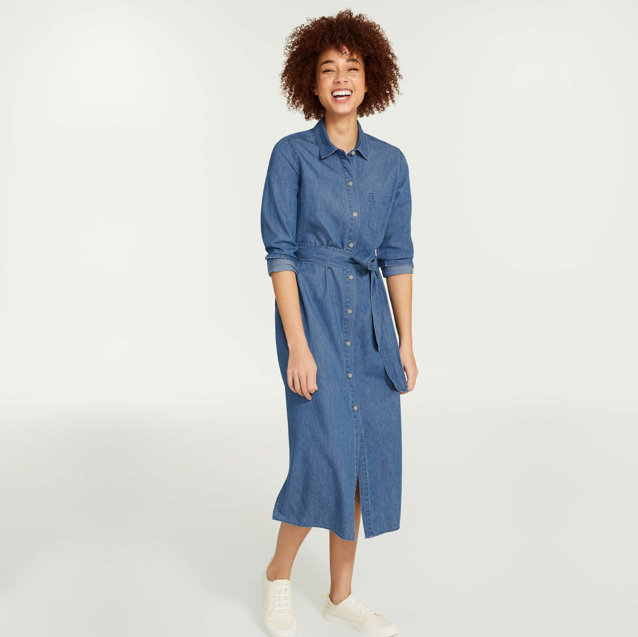 A person wearing a long denim shirtdress with rolled up sleeves