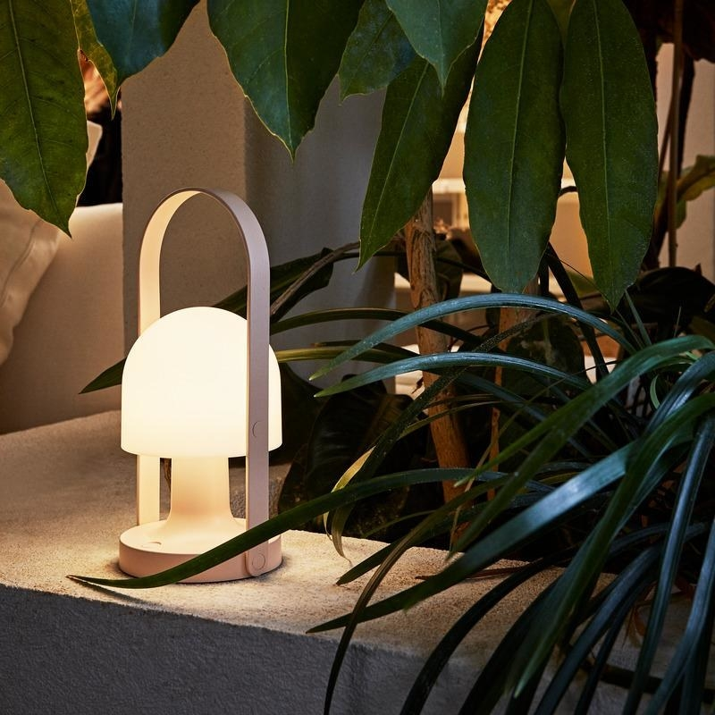 the pink Marset FollowMe Portable LED Lamp turned on on top of a concrete bench amidst plant leaves