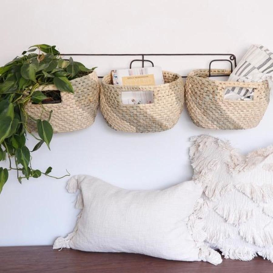 The wall rack holding a plant, blanket, and other items in its three baskets