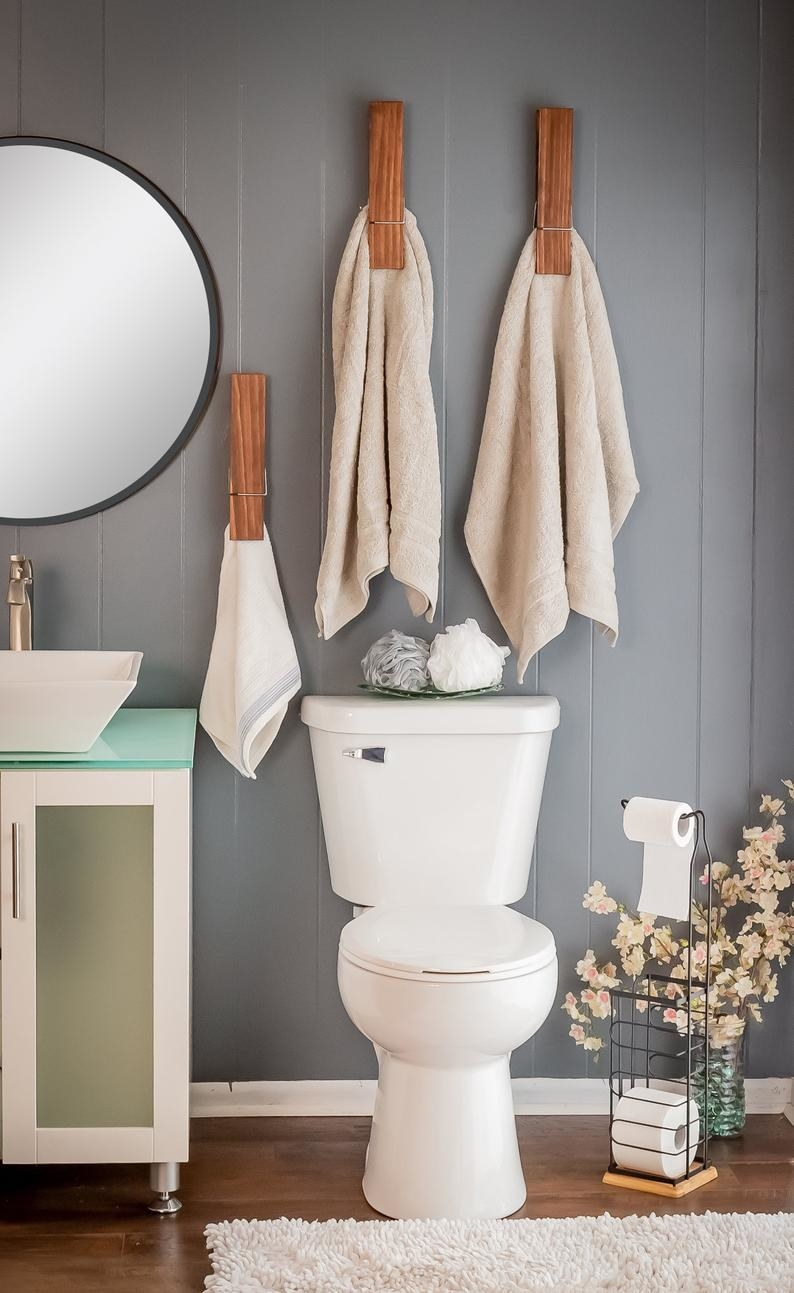 giant clothespin towel holders clasped onto large towels above a toilet