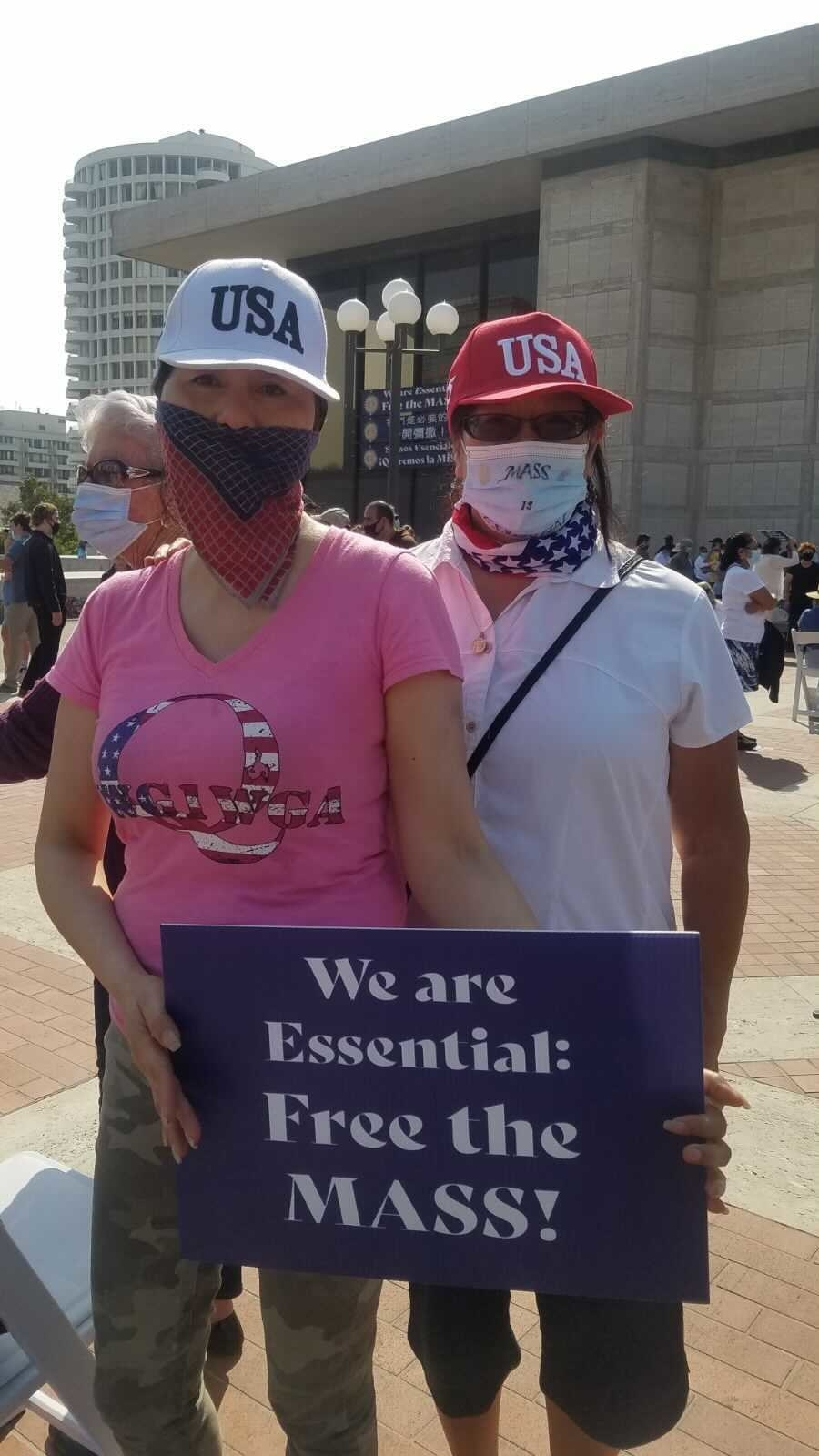 "A sign says ""we are essential: free the mass"""