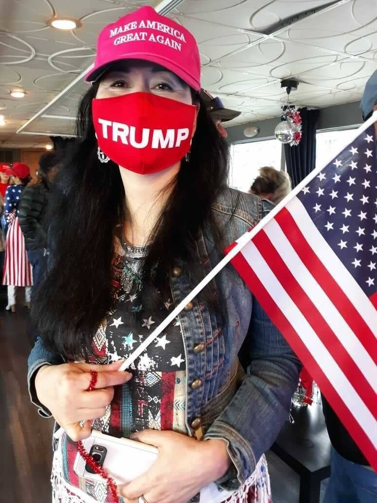 She wears a Trump face mask and holds an American flag