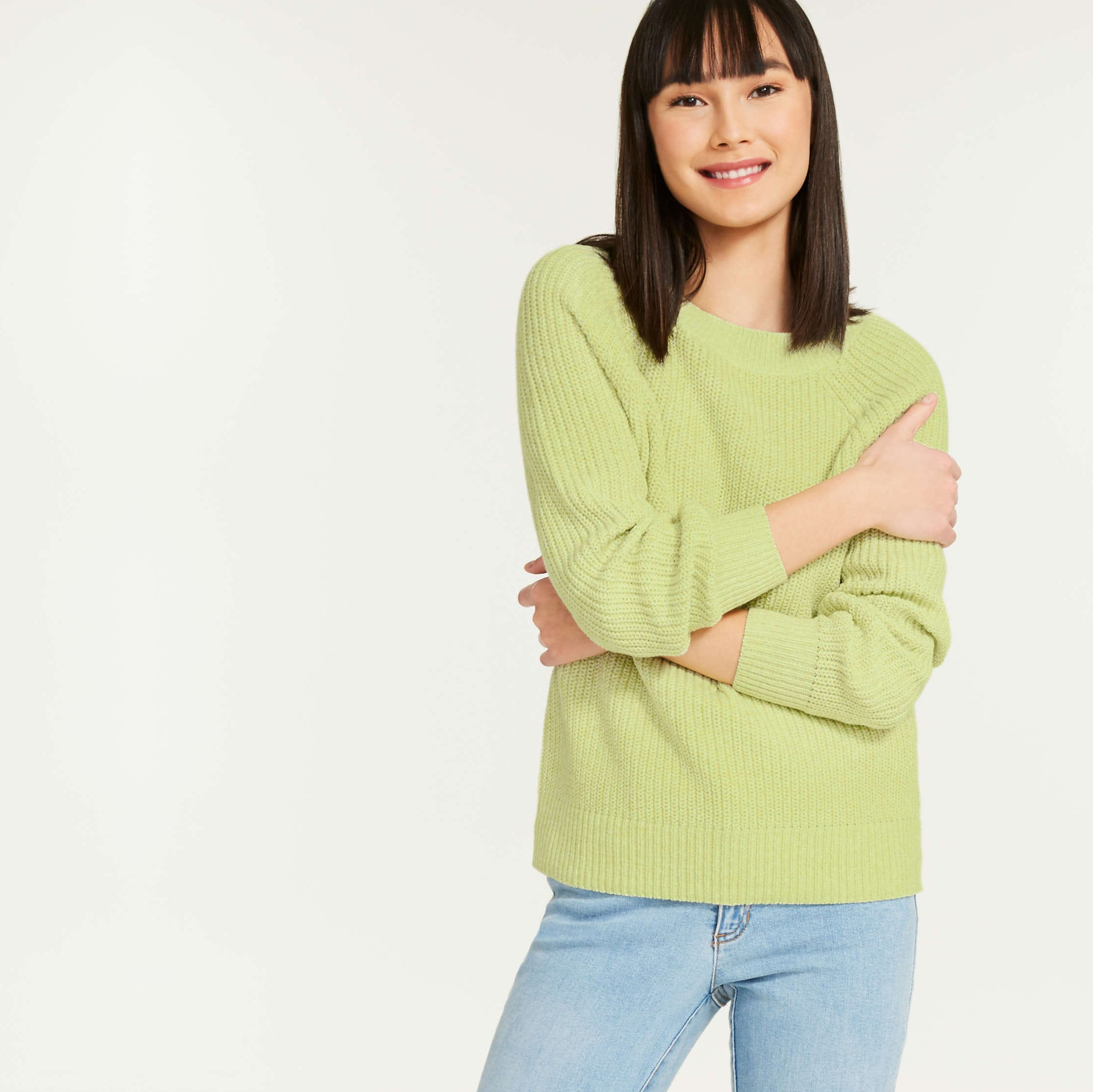 A person wearing a chunky knit sweater with jeans