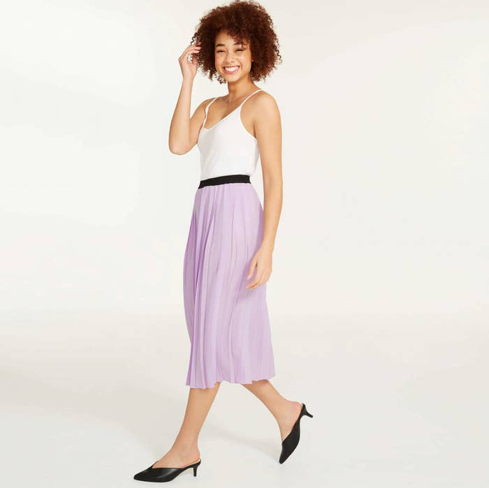 A person wearing a tank top and long skirt with low heeled mules