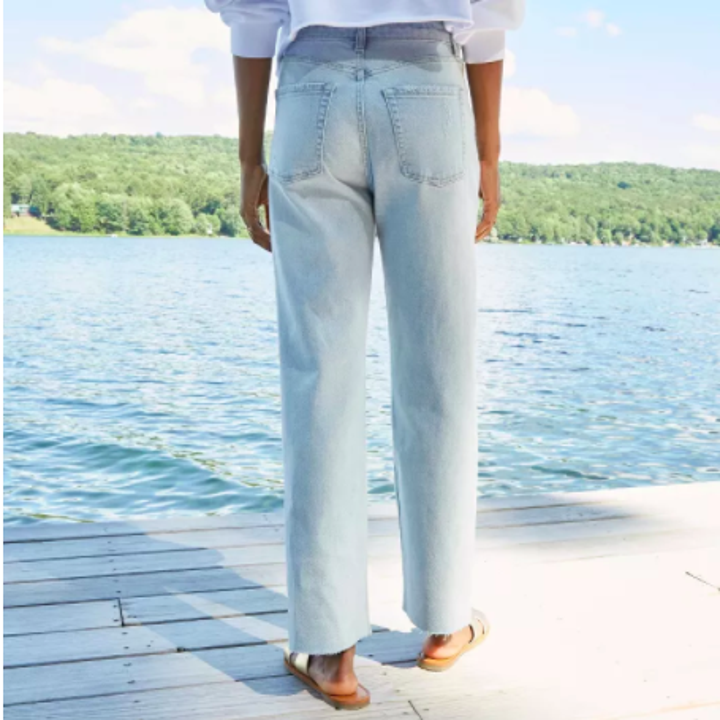 a model wearing the pants in a light wash shown with their back facing a lake