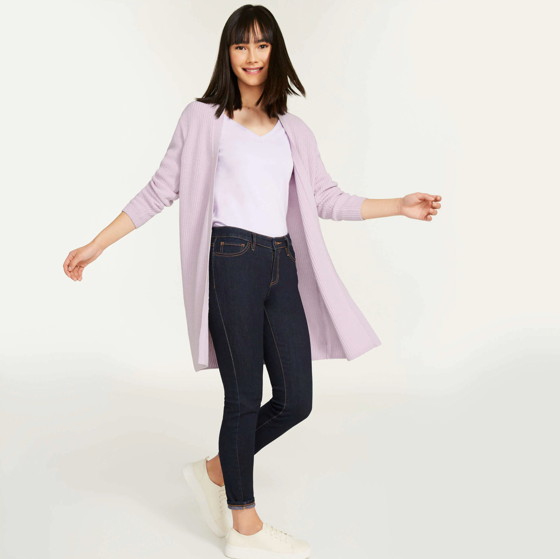 A person wearing a long cardigan over a T-shirt and jeans