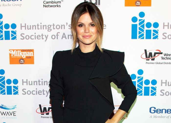 Rachel poses on a red carpet wearing a black long sleeve dress