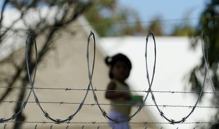 A child stands in the background, out of focus, between loops of barbed wire on a fence in the foreground