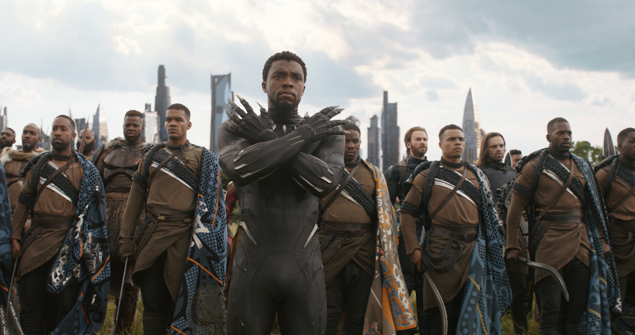 Boseman doing the 'Wakanda Forever' salute as fighters stand behind him in Black Panther in Avengers: Infinity War
