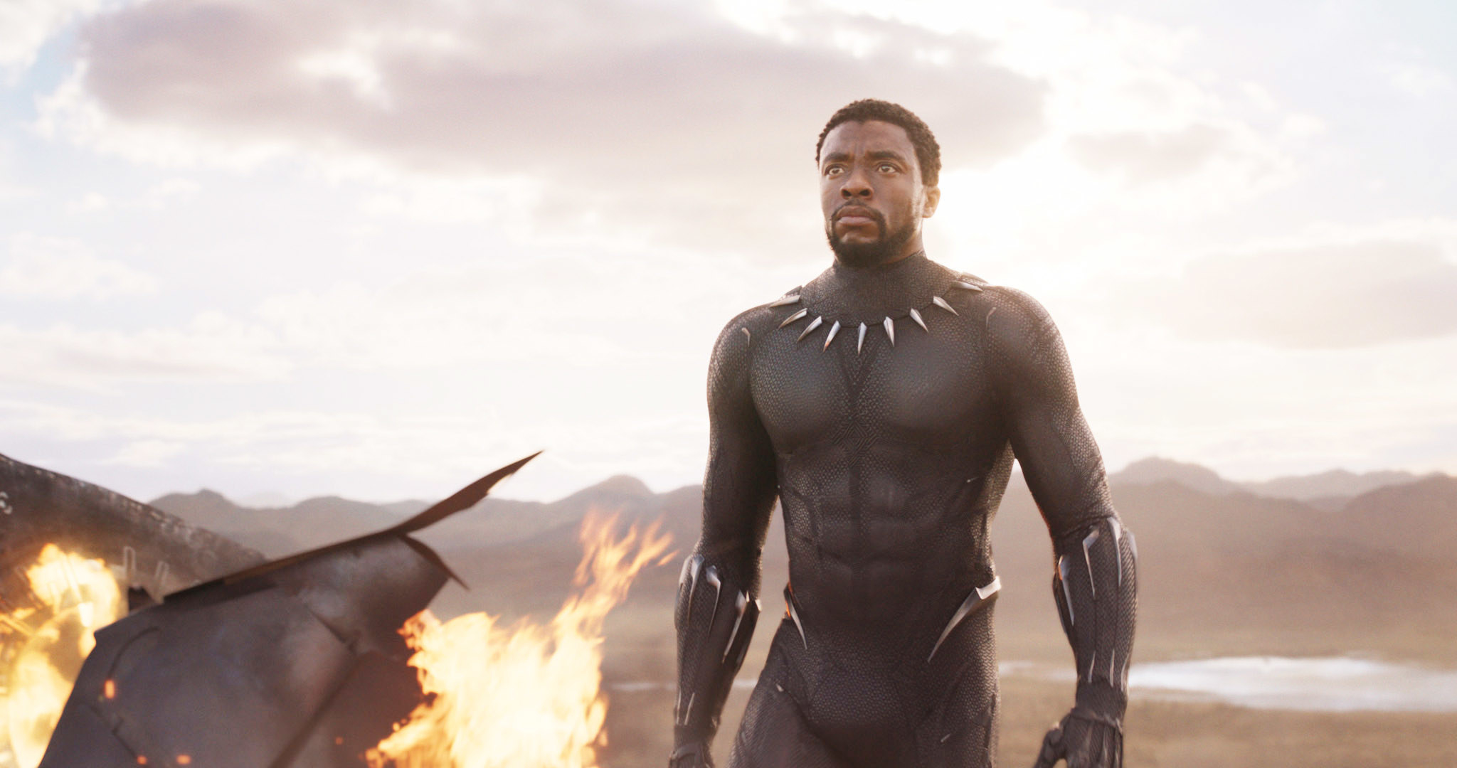 Boseman standing next to a structure that's on fire in Black Panther