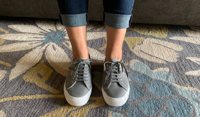 reviewer wearing grey superga sneakers