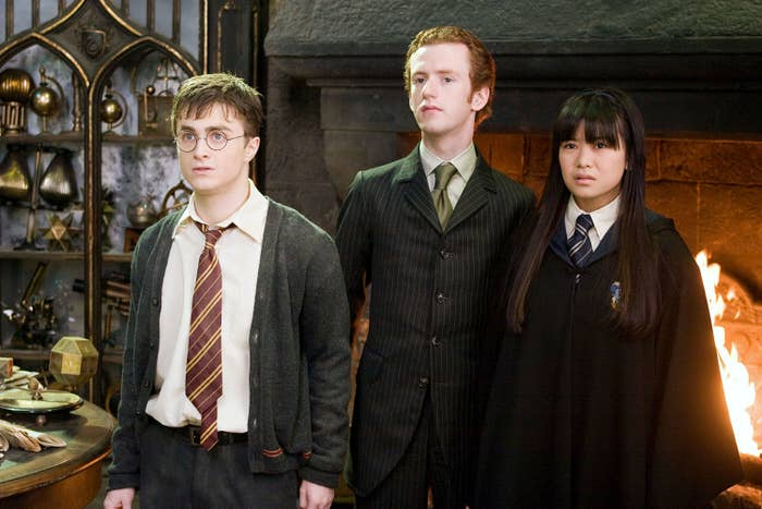 Daniel Radcliffe, Chris Rankin, and Katie Leung standing in front of a roaring fireplace in Harry Potter and the Order of the Phoenix