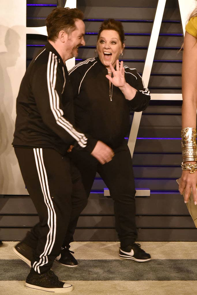 Melissa waves at someone as she and Ben walk the red carpet at the 2019 Vanity Fair Oscar Party