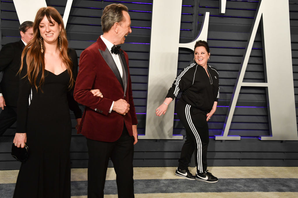 Melissa McCarthy looks behind her as she walks the 2019 Vanity Fair Oscar Party red carpet as other celebrities look on