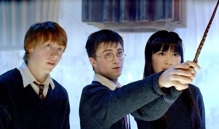 Daniel Radcliffe. and Leung holding a wand together as Rupert Grint stands next to them in Harry Potter and the Order of the Phoenix