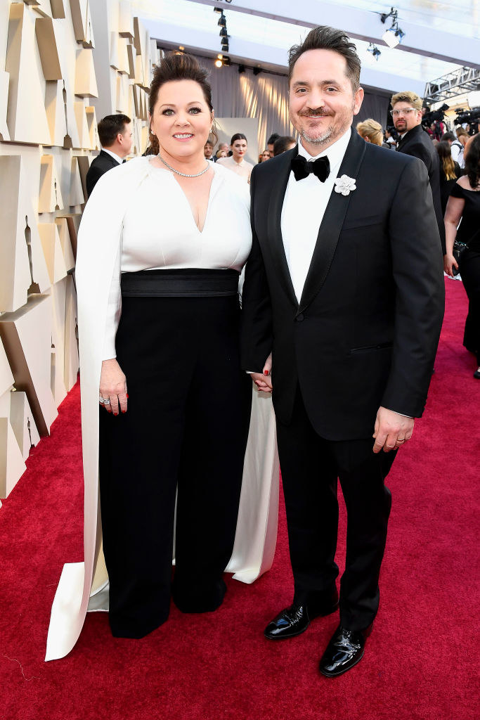 Melissa McCarthy in a black-and-white caped outfit with pearls around her neck and Ben in a tuxedo on the red carpet  at the 91st Annual Academy Awards