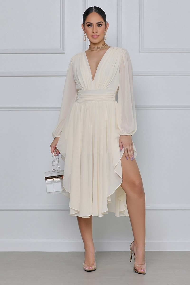A model in the ivory asymmetrical dress-like romper with plunging neckline