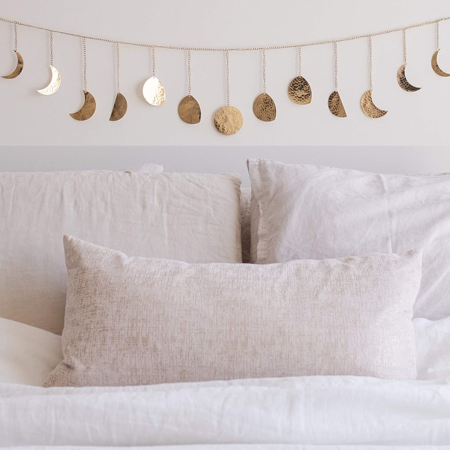 A gold moon phase garland over a bed with cream bedding