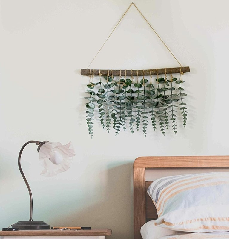 An artificial eucalyptus wall decor hanging above a bed and nightstand