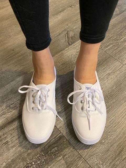 reviewer wearing white keds sneakers