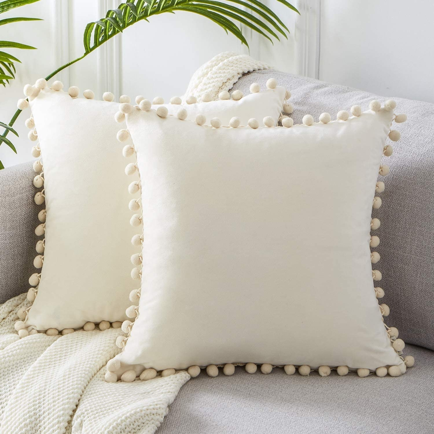 Two cream colored throw pillows with pom pom borders