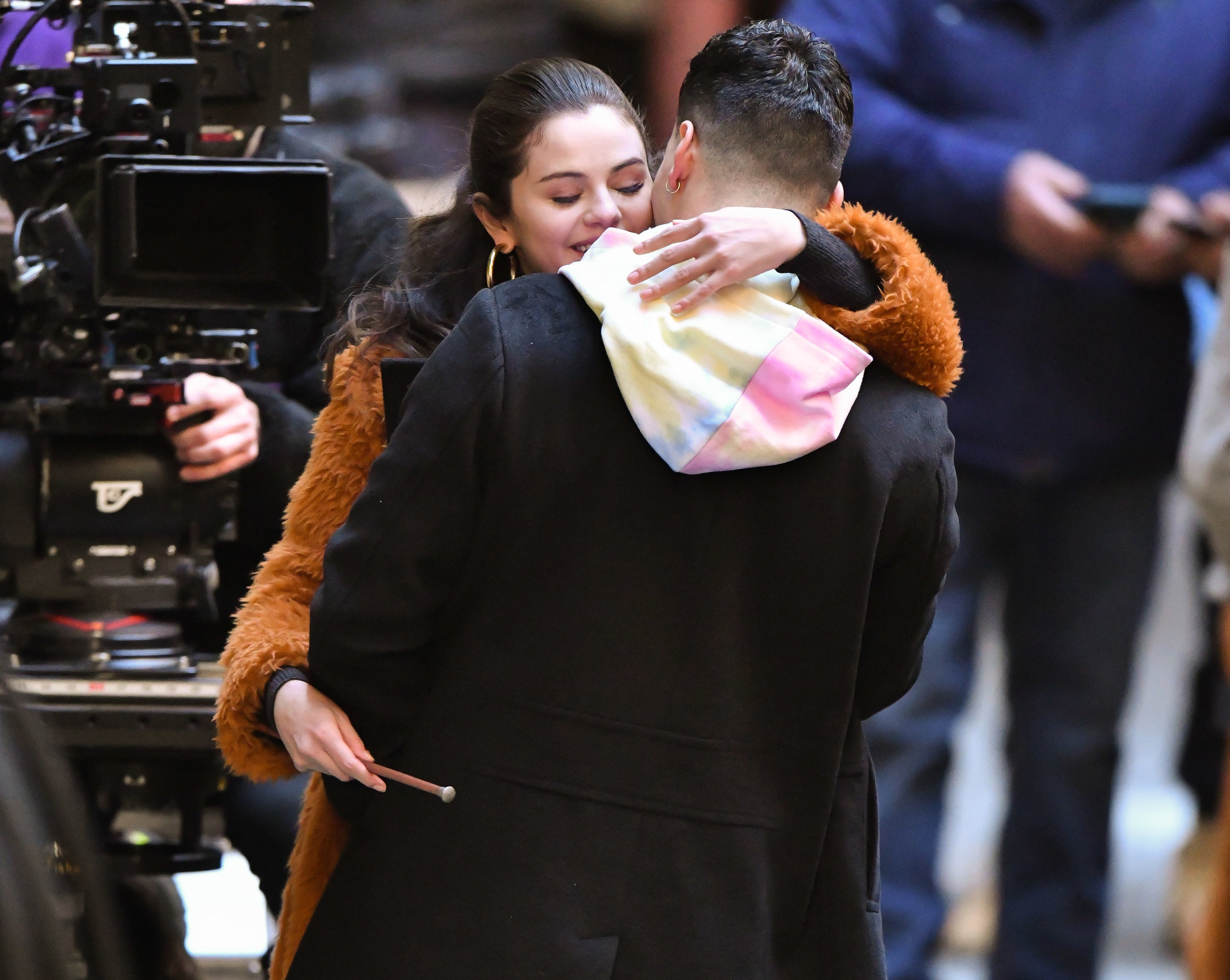 Selena and Aaron hug in front of a camera