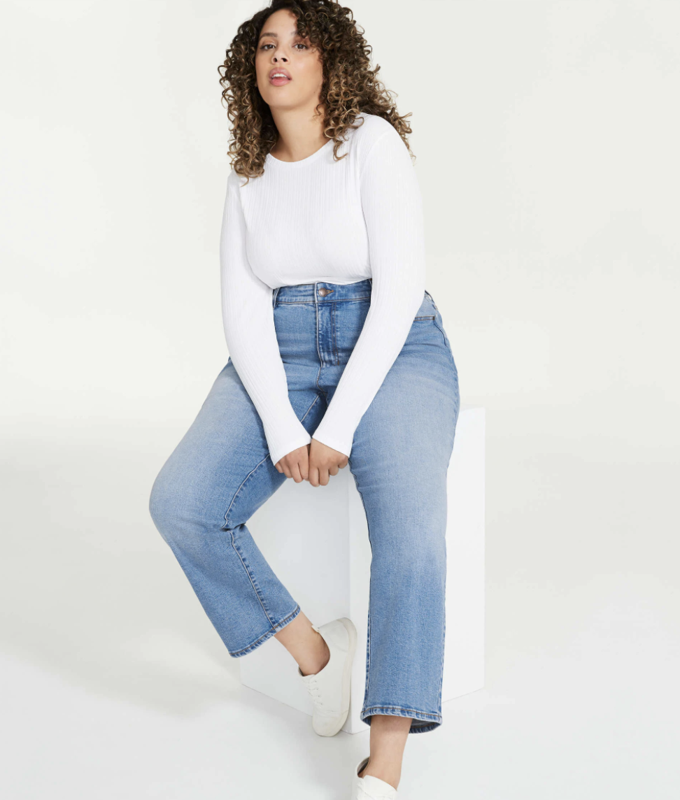 person wearing the jeans and a plain ling sleeve shirt sitting on a box