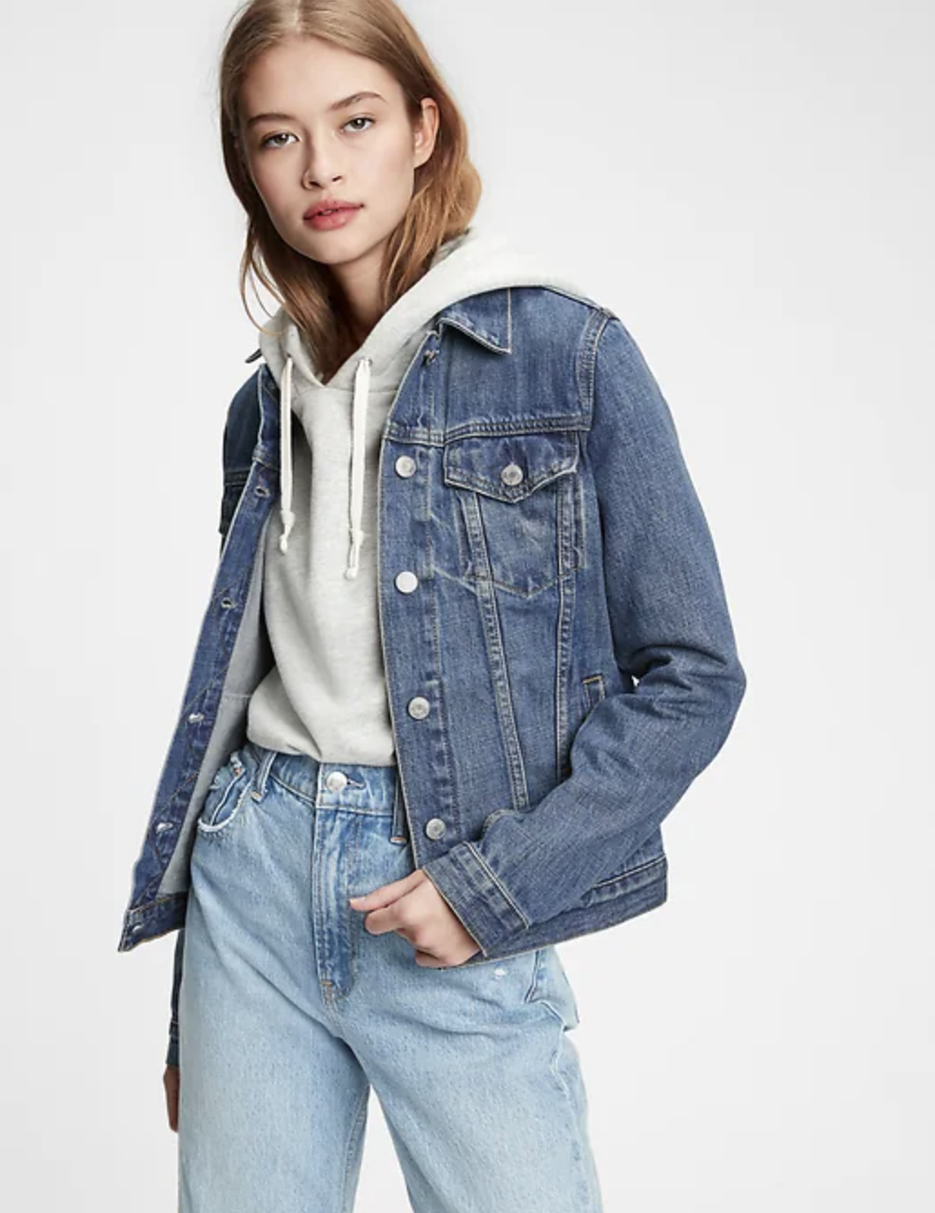 person wearing the denim jacket over a hoodie