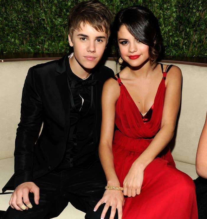 Selena sits next to Justin Bieber at an event