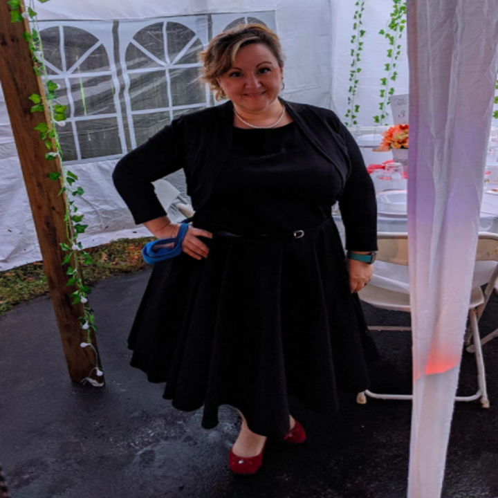 a different reviewer wearing the dress with a black sweater and belt