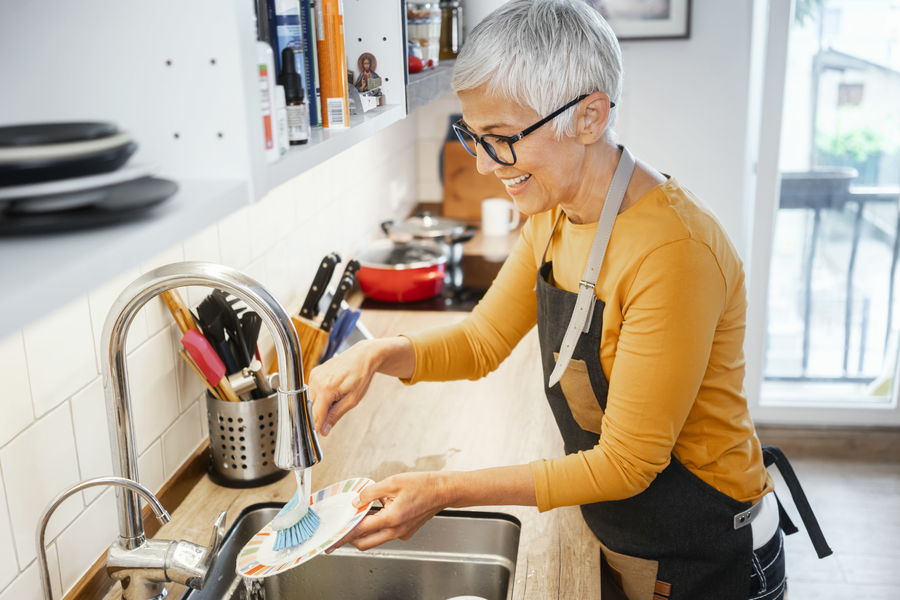 woman washing a dish in a kitchen sink