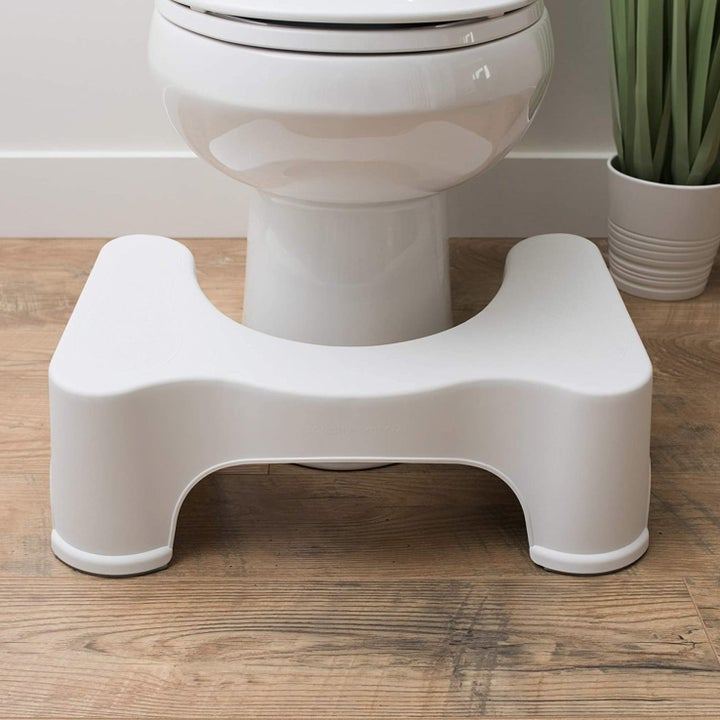 The white Squatty Potty in front of a toilet