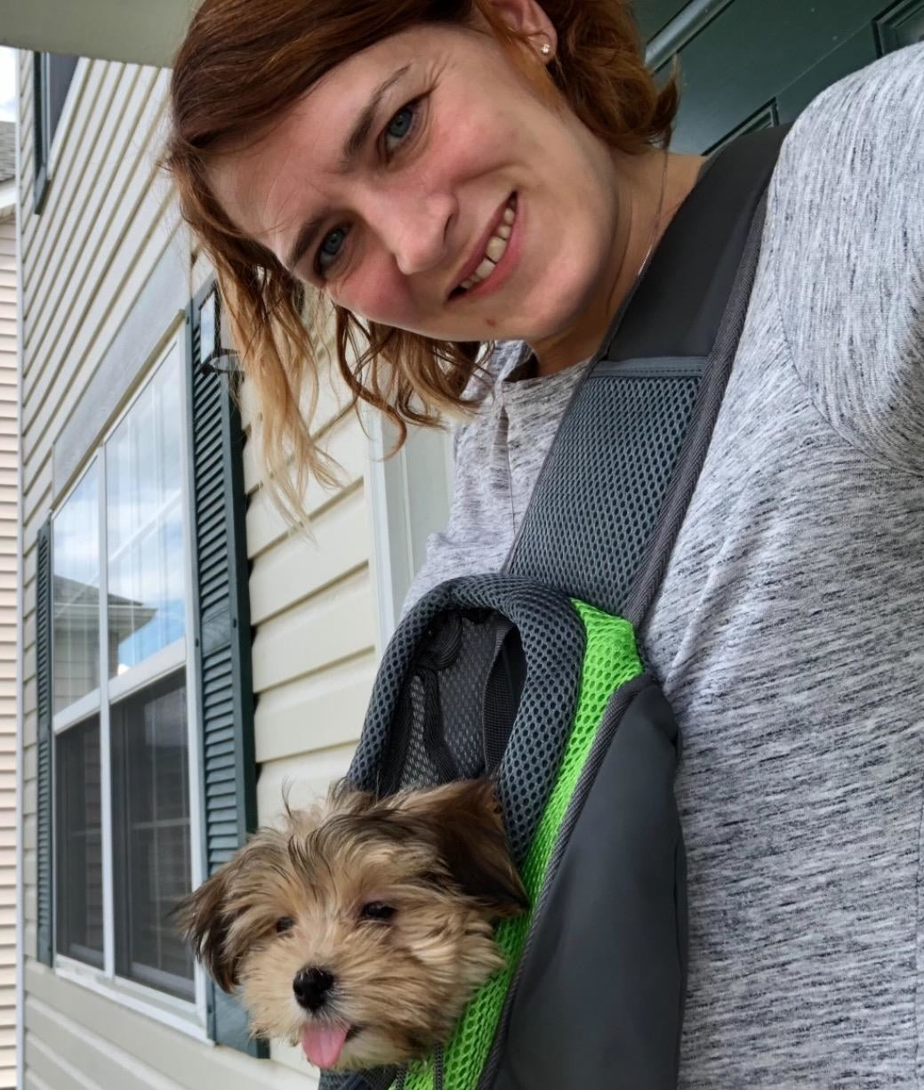 A person with a small dog in the carrier