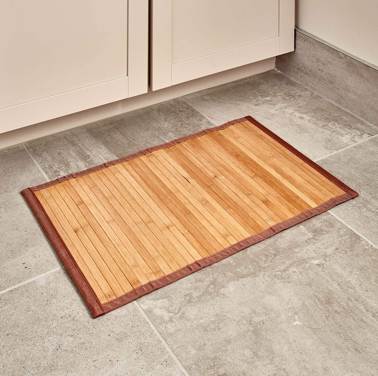 The bamboo mat in front of cabinets