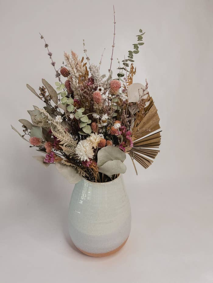 bouquet of different dried flowers and greenery in a vase