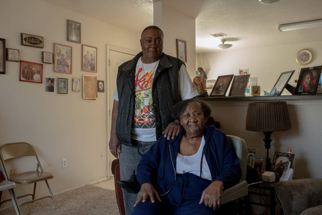 A son stands behind his mother, who is in a motorized wheelchair, as both pose in their living room, which has several family portraits on the walls and counter behind them