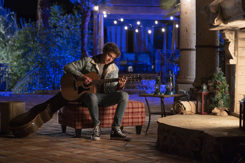Joshua playing a guitar