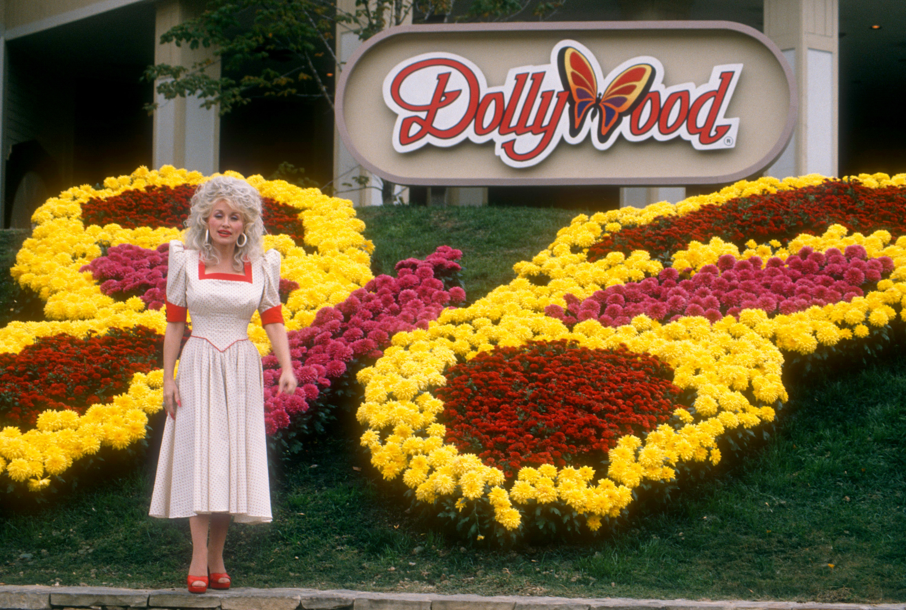 Dolly Parton standing at the gates of Dollywood.