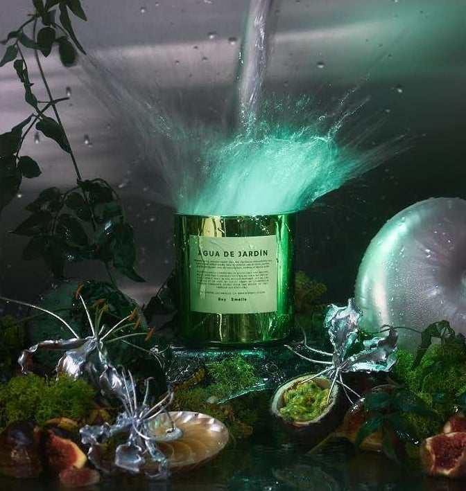 The scented candle surrounded by Botticelli-esque plant life and glittering metallic sculptures
