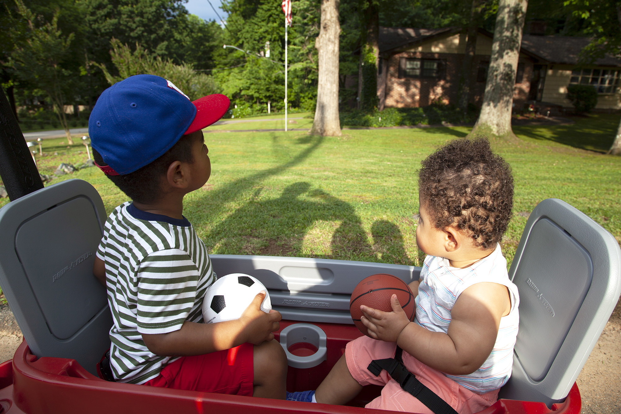 Two boys sit in a red wagon in a front yard, one carrying a small inflatable soccer ball and the other a basketball